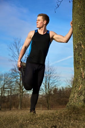 Young man streching against tree after workout photo