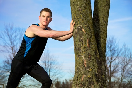 Young man streching against tree after workout Stock Photo - 9817288
