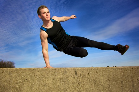 Young man jumping over wall on obstacle course photo