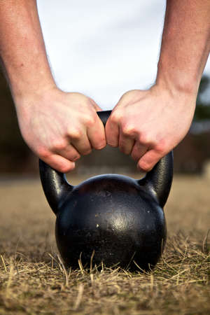 kettle: Closeup of hands lifting a heavy kettlebell