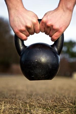 kettles: Primer plano de las manos levantando una pesada kettlebell