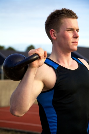 six pack abs: Young man doing kettlebell exercise outside