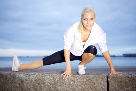 Beautiful woman doing stretching exercise on beach. photo