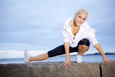 Fitness girl doing stretching exercise at the beach.  photo