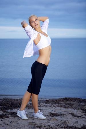 Beautiful fitness woman posing on the beach.  photo