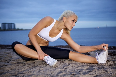 Young fitness woman stretching on a beach. photo