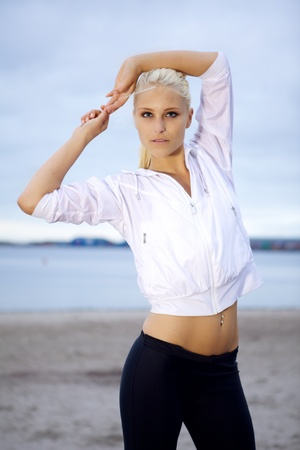 Young beautiful woman doing pilates and yoga workout on beach.  photo