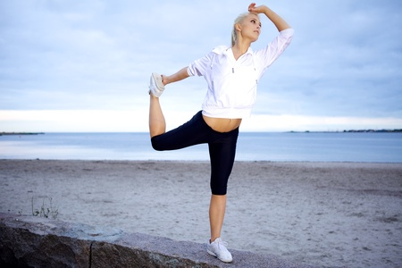 Fit girl doing an expert yoga pose on a beach. Stock Photo - 10586643