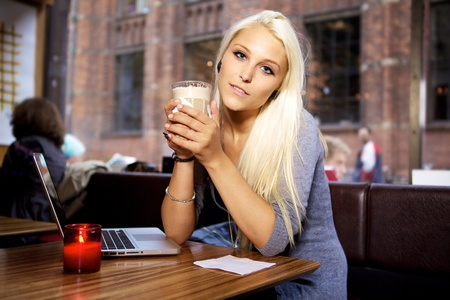 Woman sitting on a cafe with her laptop and drinking a cup of coffee. photo