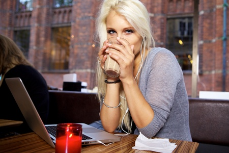 internet cafe: Hermosa mujer joven con un descanso para tomar caf� en una cafeter�a.