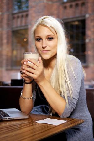 tabla de surf: Ni�a sonriente sentado en una cafeter�a con una taza de caf�.
