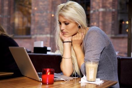 beauty shop: Mujer busca en su computadora port�til en un caf�.