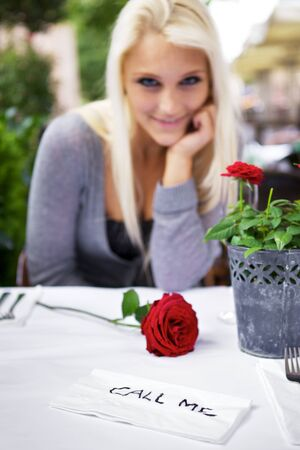 Beautiful woman on a restaurant wrote a 'call me' note on a napkin. Stock Photo - 10690719