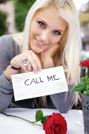 Beautiful woman on a restaurant wrote a 'call me' note on a napkin. Stock Photo - 10690716