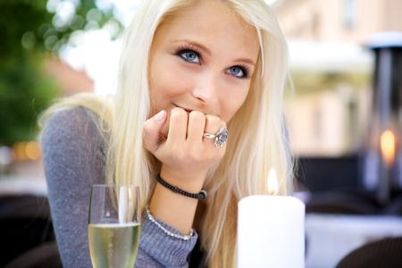 luz de velas: Retrato de joven bella mujer sentada en una mesa con una copa de champán.
