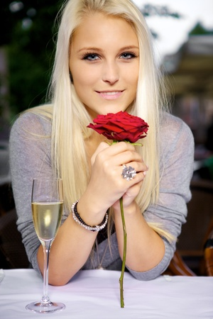 single woman: Portrait of young beautiful woman holding a red rose at a restaurant.