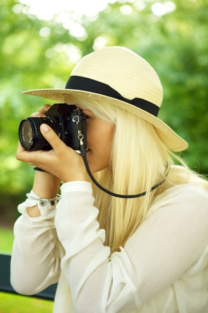 outside shooting: Young beautiful woman taking a picture in a park.  Stock Photo