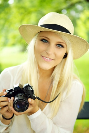 photo shooting: Portrait of a beautiful smiling female with a camera.