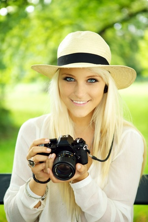 photo shooting: Portrait of a cute girl with an old-fashioned SLR camera.