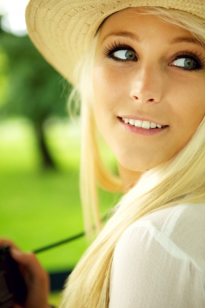 photographing: Close-up portrait of young woman with camera