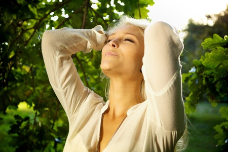 Woman standing amongst trees and relaxing. photo