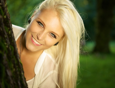 jungle girl: Close-up portrait of a cute smiling female in a forest.  Stock Photo