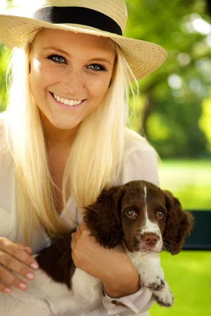 english girl: Young female sitting with a puppy on a park bench.