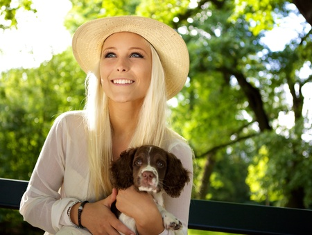 springer: Cute woman holding a English Springer Spaniel puppy in her arms on a park bench.