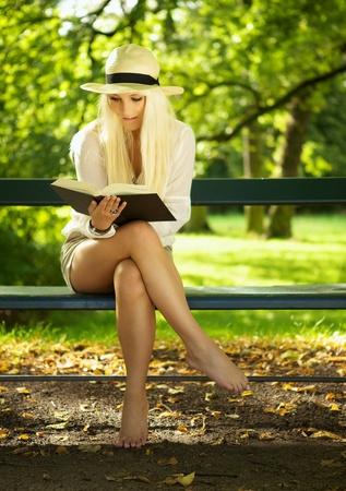 mujeres sentadas: Mujer sentada en un banco del Parque y leyendo un libro.