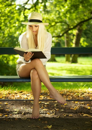 sitting in the bench: Woman sitting on a park bench and reading a book.  Stock Photo