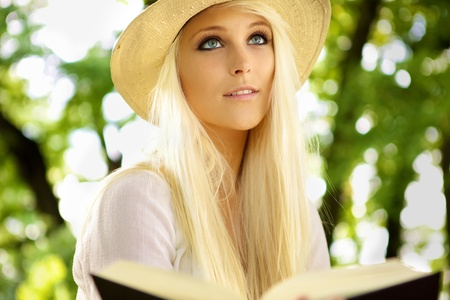 Portrait of a natural and cute woman sitting in on a park bench and reading a book. photo