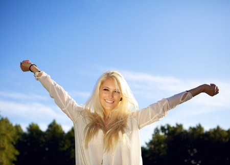 Cute smiling female in a park on a sunny day. Enjoying the sun.  photo