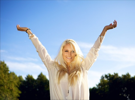 arms above head: Cute young female outside on a sunny day, raising her arms above her head.