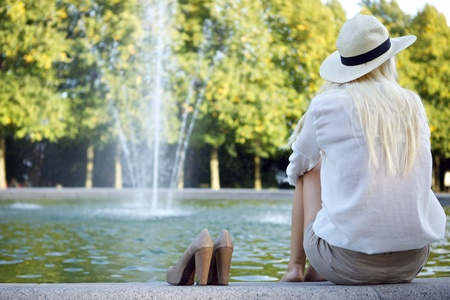 back views: Woman in light clothes sitting at a fountain and waiting