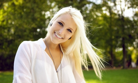 pretty blonde girl: Portrait shot of a beautiful young woman smiling. Wind blowing in her hair.