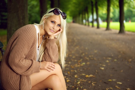 knitwear: A stylish glamorous blonde woman sits in an empty tree-lined park avenue enjoying the peace and solitude.