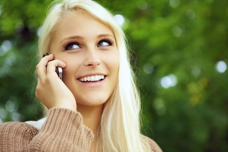 blue eyed: Face of beautiful happy young blonde girl using a cellphone and smiling with green foliage behind.