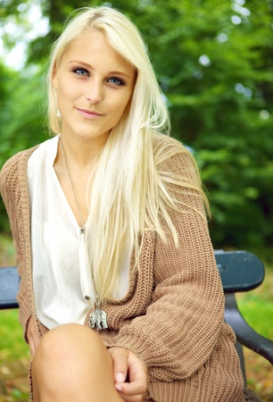 tantalising: Serene beauty, an enigmatic sexy young blonde model sits on a park bench in a tan jersey. Stock Photo