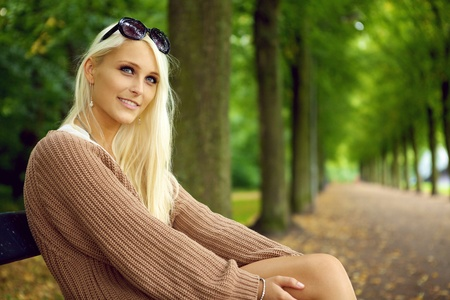 An attentive sexy young blonde woman in a tan jersey sits on a park bench looking upwards with empty tree lined avenue behind. Stock Photo