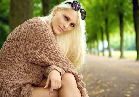 fair haired: A beautiful young blonde woman sits in a park enjoying the quiet beauty of her surroundings, beauty in nature and humans.