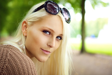 inscrutable: Close up of the face of a sexy blonde lady with sunglasses balanced on top of her forehead in a park. Stock Photo