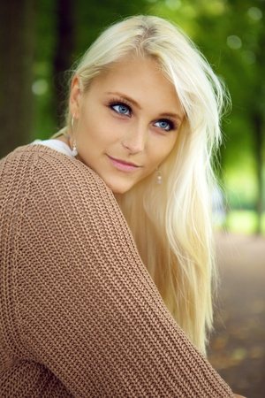 blonde haired: A beautiful blue-eyed young blonde woman gazes intently in to the distance in a park, close up face.