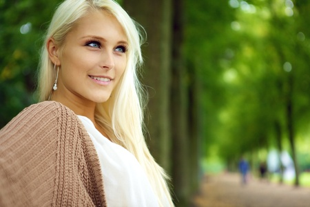 blonde haired: Face of an attractive confident self-assured young blonde woman in a tree-lined park avenue.