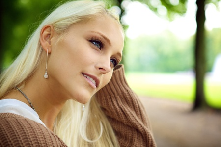 wistful: Face of beautiful young blonde female model daydreaming in wistful contemplation in a park. Stock Photo