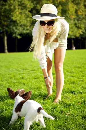 bending forward: Beautiful happy young blonde woman bending forward and playing with her dog in a park.