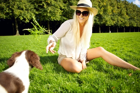 springer: A laughing young glamorous blonde lady enticing her dog sitting in a lush grassy park.