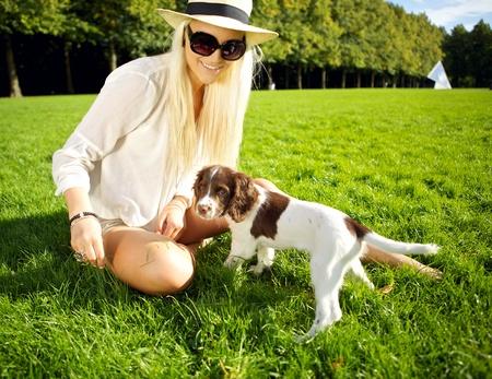 Eine stilvolle junge blonde Frau sitzt in saftigem Gras spielt mit ihrem Hund in der Abendsonne in einem Park.