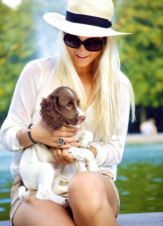springer: A smiling happy blonde lady looking down and interacting with a pet dog on her lap.