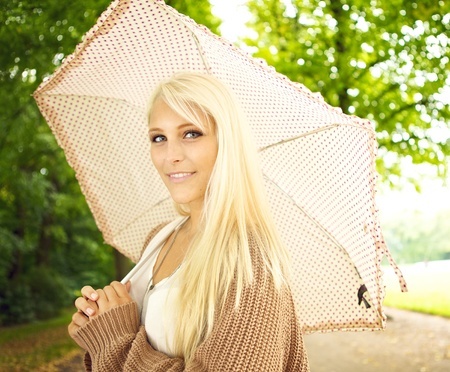 Beautiful busty young blonde girl with umbrella under trees in park. photo