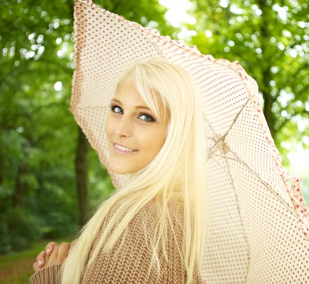 Young sexy blonde woman holding umbrella looking teasingly over her shoulder as she flirts in park. photo